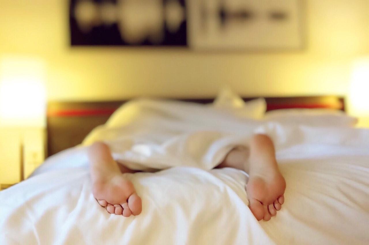 Person sover med en for kort dyne